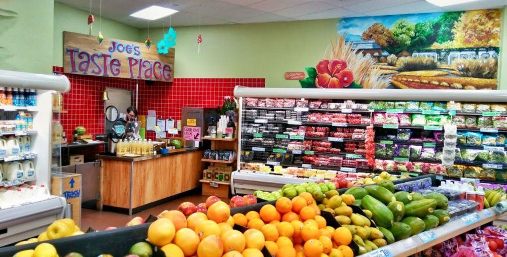 "The view in the fruits and refrigerated section, also depicts ""Joe's Taste Place""."