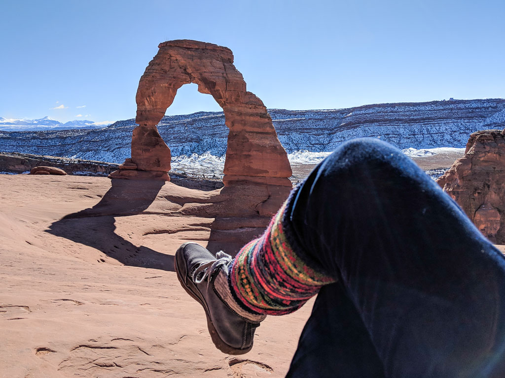 Molly's view of Delicate Arch at Arches National Park, with snow-covered mesa in the background and her leg in the foreground.