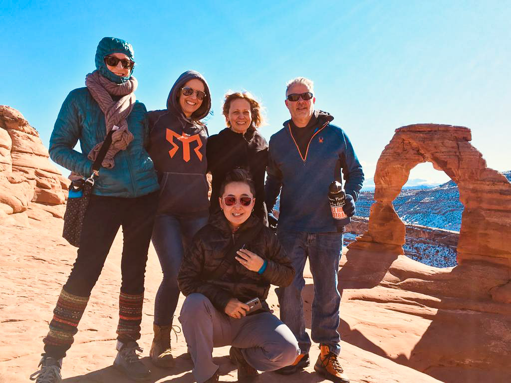 Wind-blown and bundled up Molly, Kellie, Luanne, Jen and Dennis at Delicate Arch.