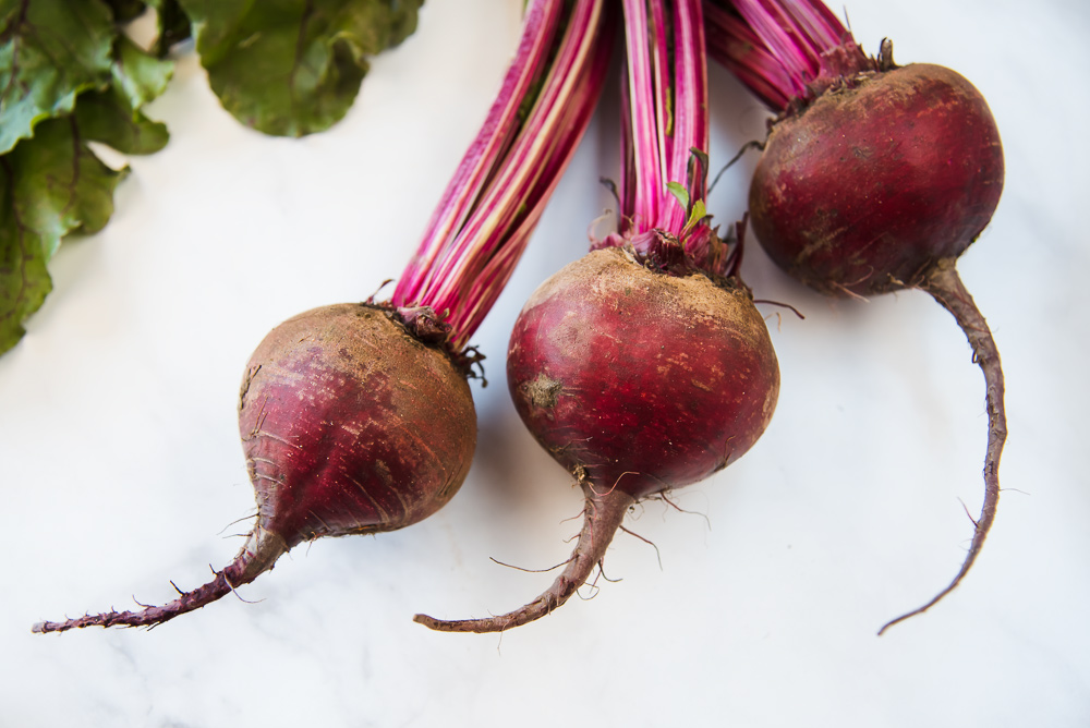 Three beet bulbs with the stems still attached.