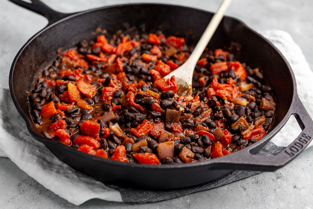 cooking beans and tomatoes in cast iron skillet plant based recipe
