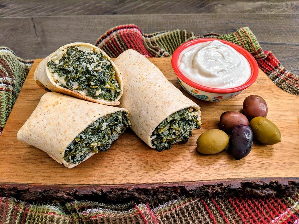 vegan plant based Handheld Spanakopita Pies with Lemony Yogurt-style Sauce and Greek Olives